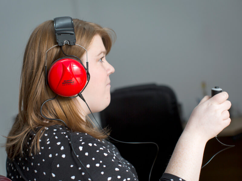 A female taking a hearing test.