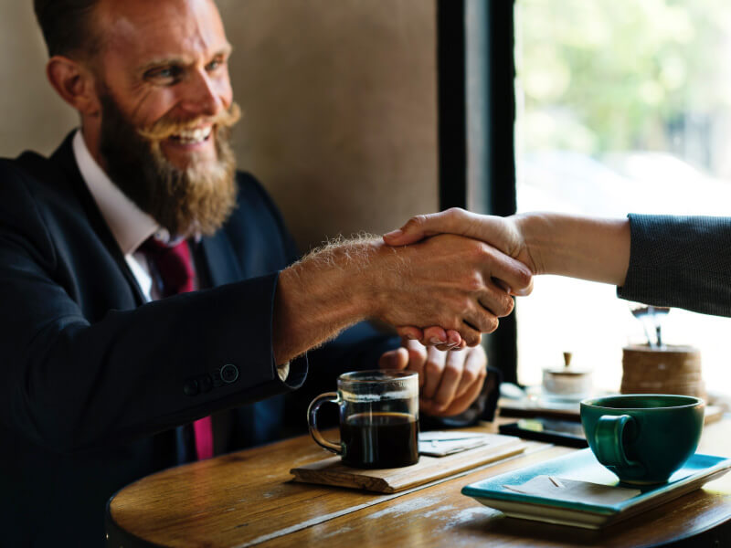 A bearded employee shaking hands with a colleague.